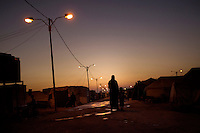 A woman and her child walk through Zaatari Refugee Camp at dusk. Approximately two million people have fled the conflict in Syria. At least 130,000 of them live in Zaatari Refugee Camp, although it was designed to house 60,000, and a further 2,000 people arrive each day.