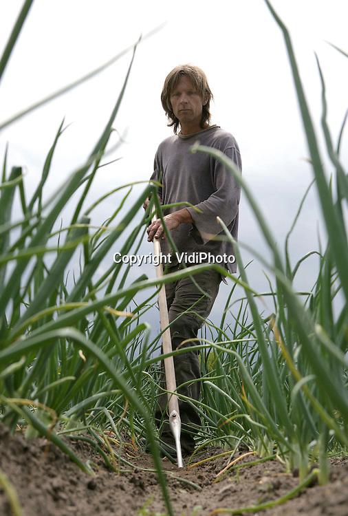 Foto: VidiPhoto..WAGENINGEN - Klaas Nijhof aan het werk in zijn groententuin..