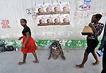 A woman begs on a sidewalk in Port-au-Prince, Haiti, under posters announcing a crusade by conservative U.S. evangelist Franklin Graham..