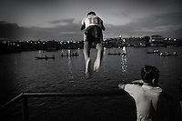 Iquitos, Peru, Jan. 14, 2007 - Boys dive from the rails of the San Francisco Church located over the Itaya River in Belen, during the late evening before mass. Because of its concrete steps the church is a popular spot for evening swimmers and bathers.