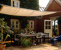 On the terrace to the rear of this country house a Yorkshire Terrier relaxes in the shade cast by a large canvas awning