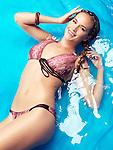 Smiling young woman wearing bikini swimsuit lying in blue water