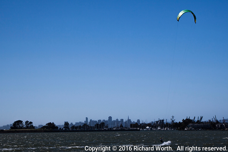 A kiteboarder on San Francisco Bay along Crown Memorial State Beach in Alameda, California, with the San Francisco city skyline in the background.