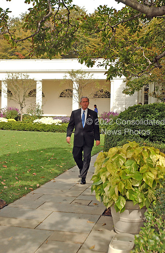 United States President George W. Bush walks through the Rose Garden at White House in Washington, D.C. on October 18, 2004.  The President was walking to Marine One for departure to a campaign event in New Jersey.  National Security Advisor Condoleezza Rice can be seen behind the President walking along the Colonnade.<br /> Credit: Ron Sachs / CNP