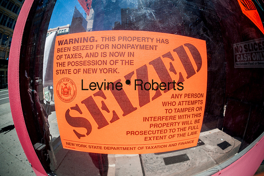 A seized sign decorates the door of Grimaldi's pizzeria in Chelsea in New York, seen on Monday, August 22, 2016. The Manhattan branch of the iconic Brooklyn eatery has been seized by the NYS Dept. of Taxation and Finance for non-payment of $122,000 in sales tax plus penalties. (© Richard B. Levine)