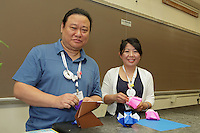 Red Paper (Seo Won Seon) and White Paper (Lee In Kyung), origami folders and designers from South Korea, prepare to teach a class how to fold Red Paper's owl design.