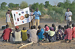 Members of an ACT Alliance team talk with villagers about the dangers of unexploded ordnance near the South Sudan town of Bor, which has been the scene of heavy fighting between government troops and rebels since a dispute within the ruling party turned violent in December 2013 and quickly ripped the newly independent nation along ethnic and tribal lines. The mine risk education team is part of the humanitarian mine action program of Dan Church Aid, a member of the ACT Alliance. The program also deploys explosive ordnance disposal teams to locate and safely remove dangerous items from this most recent conflict as well as ordnance left over from earlier decades of civil war.