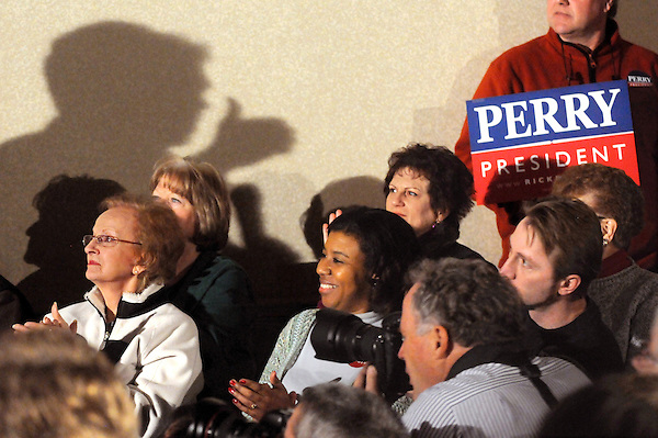 Boone, Iowa: December 31, 2011<br /> <br /> A shadow of presidential candidate Rick Perry casts upon a wall during a meet-and-greet inside the Giggln' Goat restaurant. It happened four days before the Iowa Caucus. Sitting in the middle row, left to right, are Maxinne Burma, Rita Davenport and husband Jeremy Davenport. They indicated a preference to vote for Perry at the caucus and cited their Christian beliefs as contributing to their decisions. Burma said, &quot;I think he's religious, which is what we need.&quot; .Rita Davenport said, &quot;He's a Christian. He reflects our values.&quot; Jeremy Davenport said, &quot;I'm glad he's against gay marriage.&quot; &copy;Chris Fitzgerald / CandidatePhotos