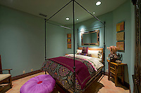 Colorful bedroom with wrought iron 4 poster bed