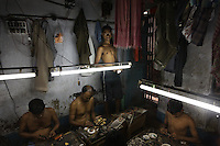 Artisanal gold smiths in Kolkata (Calcutta) work under flurescent lighting.  These guys make about 3-400 USD a month at the top end.  They live in the workplace... the clothes you see hanging above them are their clothes, their closet as it were.  At night they move the worktables aside and sleep on the floor and there are a few other places for them to crowd in to......
