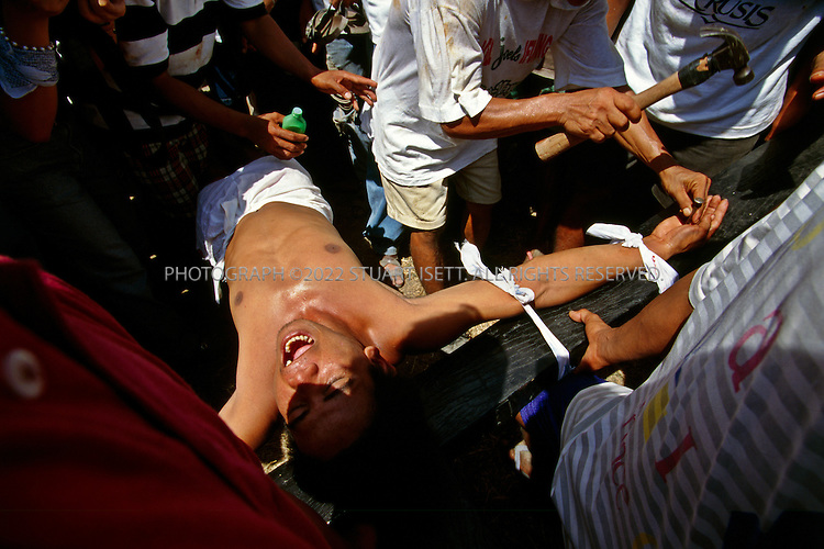 4/21/1997--San Fernando, Philippines..San Fernando is world-famous for its annual Easter re-enactment of the crucifixion of Jesus Christ. The Roman Catholic devotees were crucified in batches, their palms and feet attached to crosses with 10cm nails soaked in alcohol to prevent infection, to repent sins, pray for a sick relative or fulfill a vow, organizers said. the festival also features local men whipping themselves in penance, sending up showers of blood on visitors..Photograph ©2007 Stuart Isett. All rights reserved.