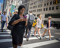A pedestrian checks her smartphone while crossing a Fifth Avenue intersection in New York on Thursday, July 23, 2015. (© Richard B. Levine)