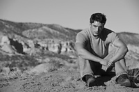 Young man sitting in the desert with his hands clasped