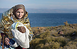A Syrian refugee woman and her baby hike up a hill from a beach near Molyvos, on the Greek island of Lesbos, on October 30, 2015. They were passengers on a boat full of refugees that traveled to Lesbos from Turkey, provided by Turkish traffickers to whom the refugees paid huge sums to arrive in Greece.