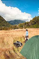Woman camping on grassy clearing next to Perth River with great mountain views, South Westland, West Coast, New Zealand