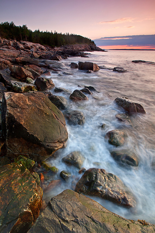 Granite boulders along the eastern shoreline of the Great Head soak up the first rays of sunrise in Acadia National Park, Maine, USA