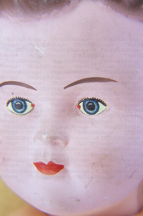 Face of vintage boy doll with bright blue fixed eyes and bright red lips