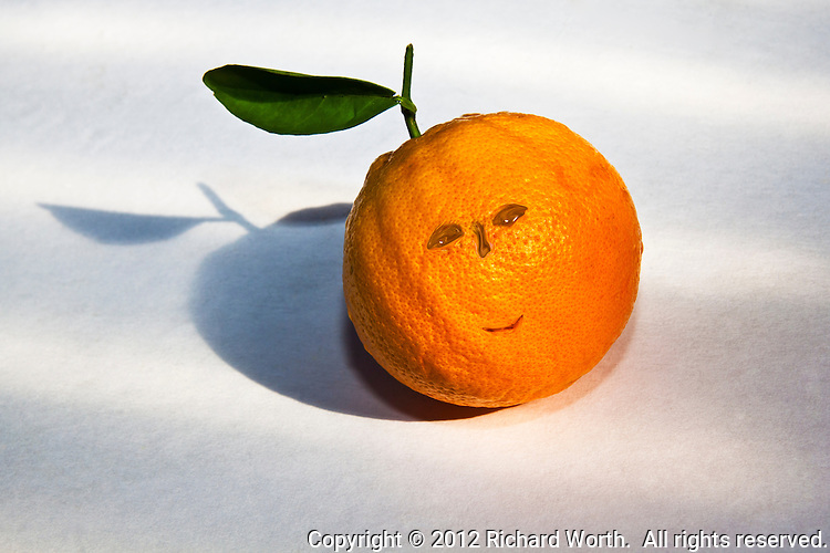 An orange with its stem and a leaf on a white background with a Photoshop tweak of blemishes in the peel creating the illusion of eyes, a nose and a grin.