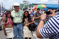 A man has his photograph taken standing between two Waorani (Huaroni) women during a parade by Waoranis from different communities through the streets of Coca to celebrate its anniversary.