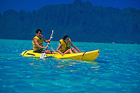 Japanese couple paddiling a yellow kayak in turquoise blue ocean, ahu o laka, Kaneohe Bay, off the island of Oahu