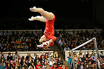Member of the Arkansas Razorback Gymnastics team competing on the uneven bars in Barnhill Arena.