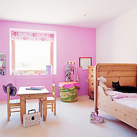 One wall of this little girl's bedroom is painted pink and has a matching floral window blind