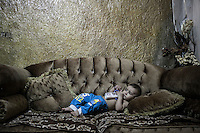 June 09, 2015 - Beirut, Lebanon: Hamza, a Palestinian refugee child and grandson of Ammal Akkar (not pictured), lays on a couch at his family house in Shatila refugee camp. (Photo/Narciso Contreras)