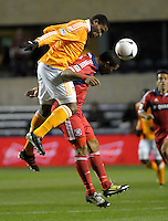 Houston defender Jermaine Taylor (4) heads the ball over Chicago forward Sherjill MacDonald (7).  The Houston Dynamo defeated the Chicago Fire 2-1 in the Eastern Conference play-in game for the MLS Playoffs at Toyota Park in Bridgeview, IL on October 31, 2012.