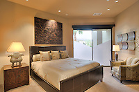 Elegant guest bedroom nicly furnished with art above headboard of bed