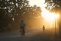 A young girl runs down the street as others cycle along during the late afternoon just outside of Inle Lake, Myanmar.