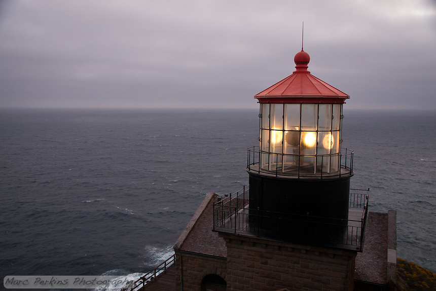 A view of the Pacific Ocean with Point Sur Light Station's light house in the foreground.  The sun has just set, and low marine clouds cover the sky, while the light can be seen rotating.  The view from the lighthouse is just stunning.  This view includes almost none of the hillside, as opposed to #2.