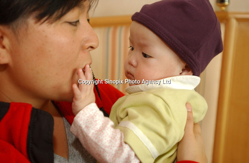 Newly adopted mother and daughter  interact during the first 24 hours of the first restless night. The family were part of a group of Canadian nationals go through the adoption procedure in Changsha, Hunan, China.