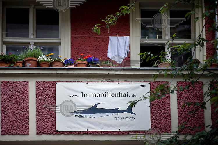 Ironic poster reading The Immobilienhai next to the new living project Choriner Hoefe at the Zehdenicker Strasse inside the popular district Prenzlauer Berg in Berlin. This modern ensemble by the company Diamona and Harnisch is a good example of the transition process concerning high rising property market in Berlin.