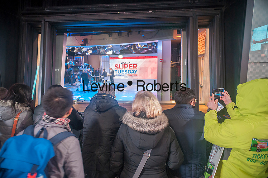 Spectators watch the ABC Eyewitness News studios in Times Square in New York as workers ready for their Super Tuesday coverage on March 1, 2016. (©Richard B. Levine)