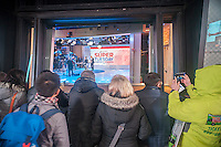 Spectators watch the ABC Eyewitness News studios in Times Square in New York as workers ready for their Super Tuesday coverage on March 1, 2016. (© Richard B. Levine)