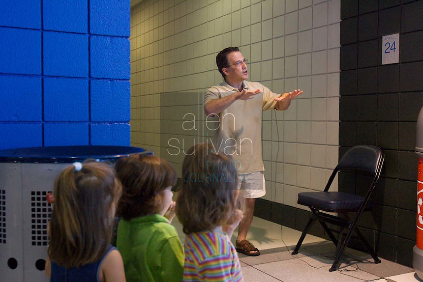 Eric Motel of Marietta gives a taped audition as his triplets watch during a Dreams N2 Reality show and casting call at Philips Arena in Atlanta on Saturday, August 4, 2007. People offered their auditions in hopes of gaining spots on game shows and others in the reality TV genre.