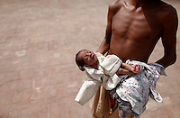 A severely malnourished baby is taken to the hospital by her brother in Pakistan's Muzaffargarh district of Punjab province September 4, 2010. The flooding has destroyed cropland and livestock and displaced millions of people, causing damage the government has estimated at $43 billion, or almost one quarter of the South Asian nation's 2009 GDP.    REUTERS/Damir Sagolj (PAKISTAN)