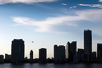 A Goodyear blimp climbs in the late-afternoon sky behind silhouetted condominium and office buildings on Miami's Brickell Avenue.