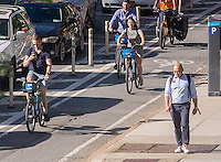 Bicycle commuters on the Ninth Avenue bike lane in the Chelsea neighborhood of New York on Friday, June 10, 2016 . (© Richard B. Levine)