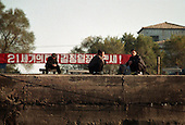 Sinuiju city, North Korea, 11-2003..North Korean men squat under a banner that reads: ?Long live the sun of the 21st century leader Kim Jong Il!?. .North Korea is the world's most insular and totalitarian state. Ruled by the messianic leader Kim Il Sung and his son Kim Jong Il since 1948, North Korea has stubbornly stuck to its juche (self-reliance) ideology and siege mentality, imposing one Stalinist economic plan after another. Floods, droughts and mismanagement in the 1990s plunged the country into a preventable famine, killing up to three million, or 13 percent of the population. It now depends heavily on Chinese aid...