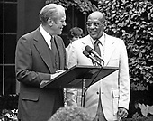 United States President Gerald R. Ford, left, and Jesse Owens, right, American track and field athlete and four-time Olympic gold medalist in the 1936 games, in the East Garden of the White House in Washington, DC during an event to honor the US stars of the 1976 Olympic Games in Montreal on August 5, 1976.  The President later presented Mr. Owens with a plaque from the US Government and praised him for his athletic accomplishments.<br /> Credit: Benjamin E. &quot;Gene&quot; Forte / CNP