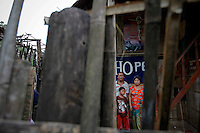 """U Tin Saung, his wife Myint Myint Yee and their son Kyao Pauk refugees from Yangon in Myanmar pose for photo under the """"hope"""" sign at their home at the Mae La refugee camp near Mae Sot June 3, 2012. Asked about Aung San Suu Kyi's visit to the camp U Tin Saung said """"There is no hope for Myanmar. Only hope for our souls. I think military will not allow Suu Kyi to have power and will make coup. Then they will be more cruel."""" Myanmar's pro-democracy leader Aung San Suu Kyi visited on Saturday Mae La, the biggest refugee camp along the Thailand-Myanmar border where tens of thousands of her compatriots found shelter after escaping from Myanmar.  REUTERS/Damir Sagolj (THAILAND)"""