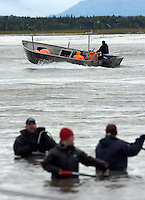 On their way to a nearby cannery, a commercial setnet fishing crew motors their catch past dipnet fishermen in the Kenai River in Kenai, Alaska. Some inlet commercial fishermen and some upstream sports fisherman are unhappy with the number of fish the personal use dipnet fishery, open to Alaskan residents only, takes.