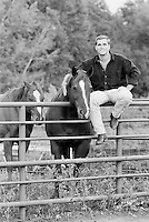 Good looking guy sitting on an iron gate with his arm around a horse