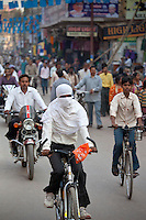 Muslim woman with hijab burkha veil covering head and face cycles in the street in city of Varanasi, Benares, Northern India