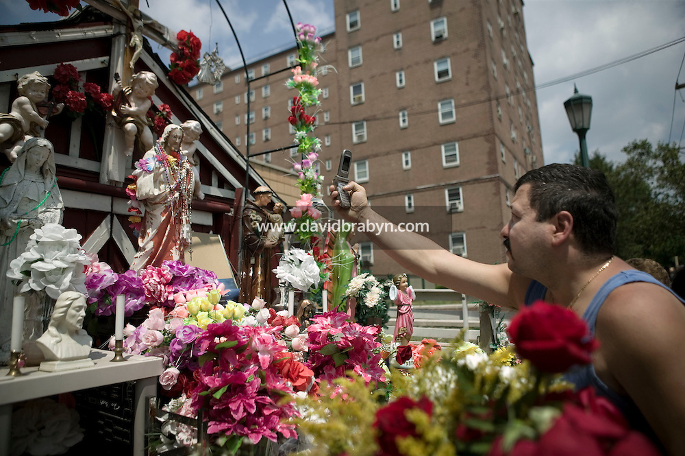 A man uses his cellphone to photograph a statue of Christ that rests in a small shrine on Jackson and Third streets in Hoboken, NJ, USA, to examine the eye that is said to have suddenly opened without human intervention a few days earlier in what locals believe is a sign from God, 31 July 2005. Photo Credit: David Brabyn