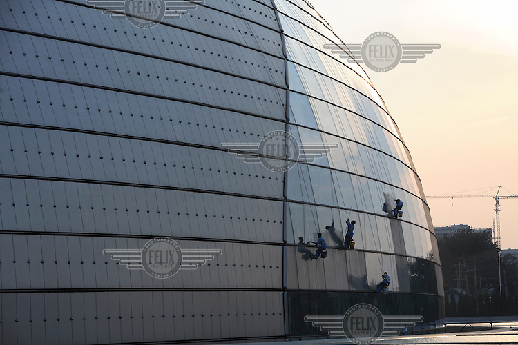 Window cleaners work on Beijing's controversial 300 million USD National Grand Theatre and opera house, also known as 'The Egg'..
