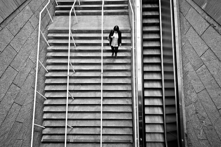 A woman on a set of stairs going down with an escalator moving upward looking at mobile phone