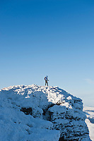 Female hiker standing on summit of Corn Du in winter, Brecon Beacons national park, Wales