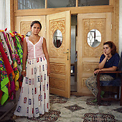 Nadia, a 14 year old Roma girl, stands beside a rack holding all her skirts, whilst a Romanian employeed as the family maid sits and watches. Two weeks after this picture was taken Nadia would be getting married. In the Roma camp of Sintesti.